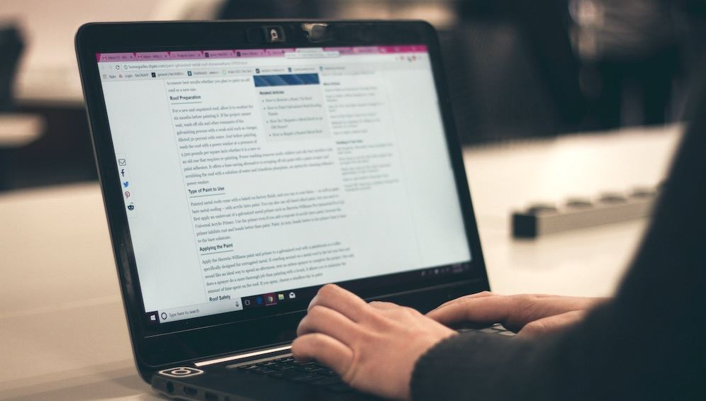 Person writing a blog post on a laptop