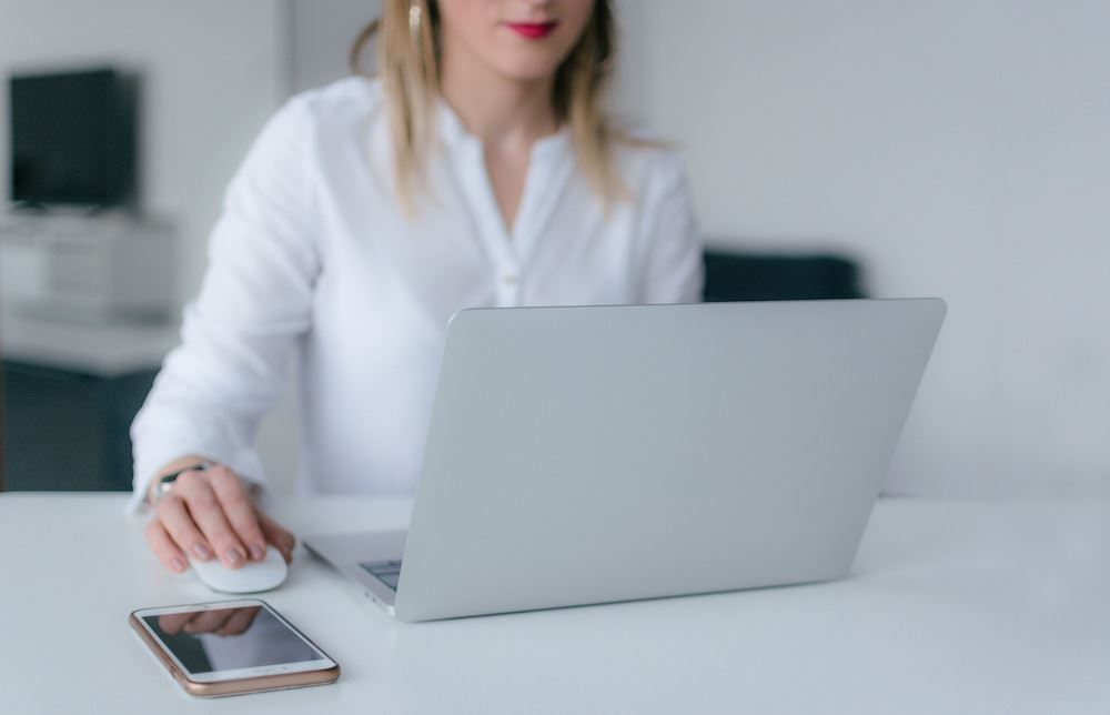 Woman wearing a white shirt working on a laptop