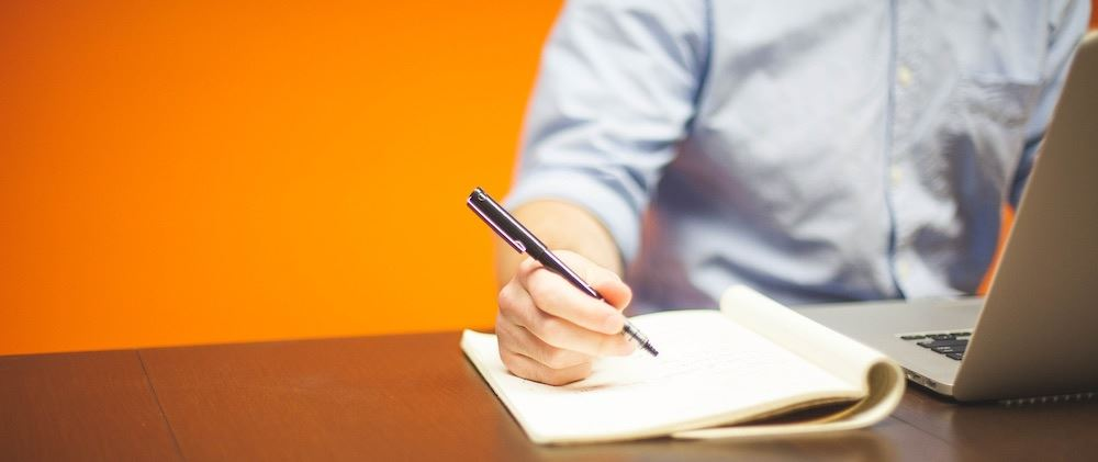 Man in front of orange wall with a laptop writing in a notebook